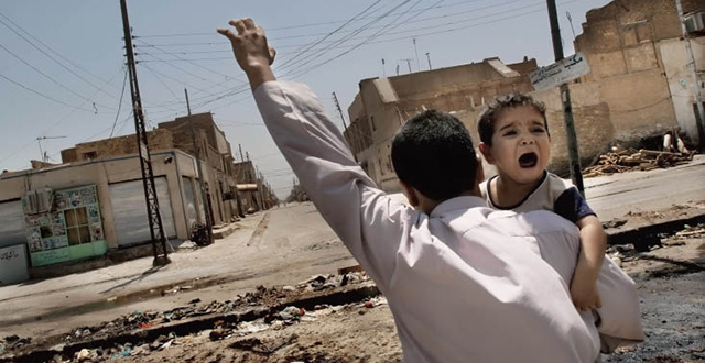 A father shows his hand to snipers as he carries his terrified child across the frontline in Najaf, 2004: Photo by Kael Alford