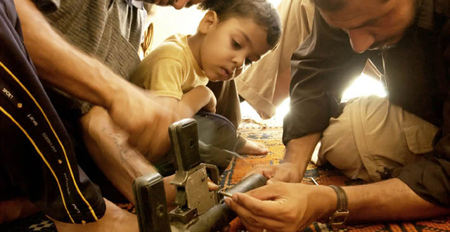 A boy watches his relatives repair a grenade launcher in Sadr City, 2004. Photo by Thorne Anderson