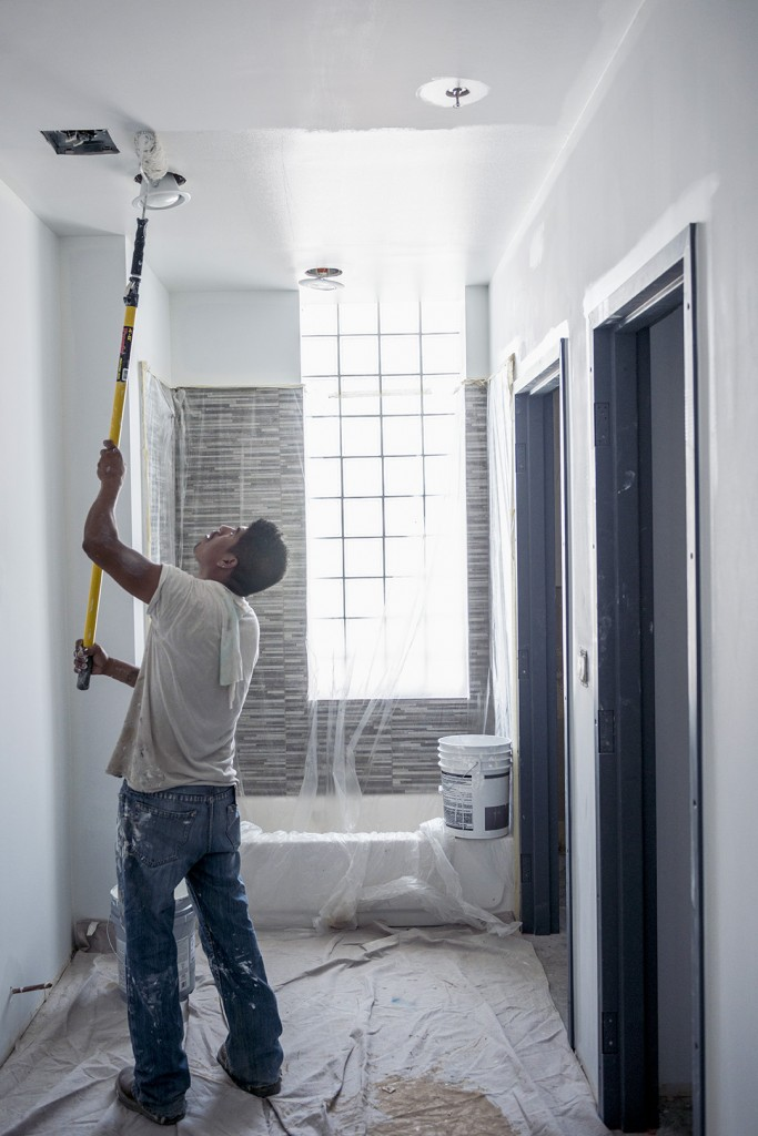 A worker paints the ceiling of a loft apartment at Jefferson Tower. Nine apartments will be available by the end of the year, and eight more early next year.