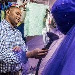 U.S. Rep. Marc Veasey steams a dress at Veronica's, a quinceañera and wedding shop on Jefferson Boulevard, as part of his pledge to spend time in his constituents' work shoes. (Photo by Danny Fulgencio)