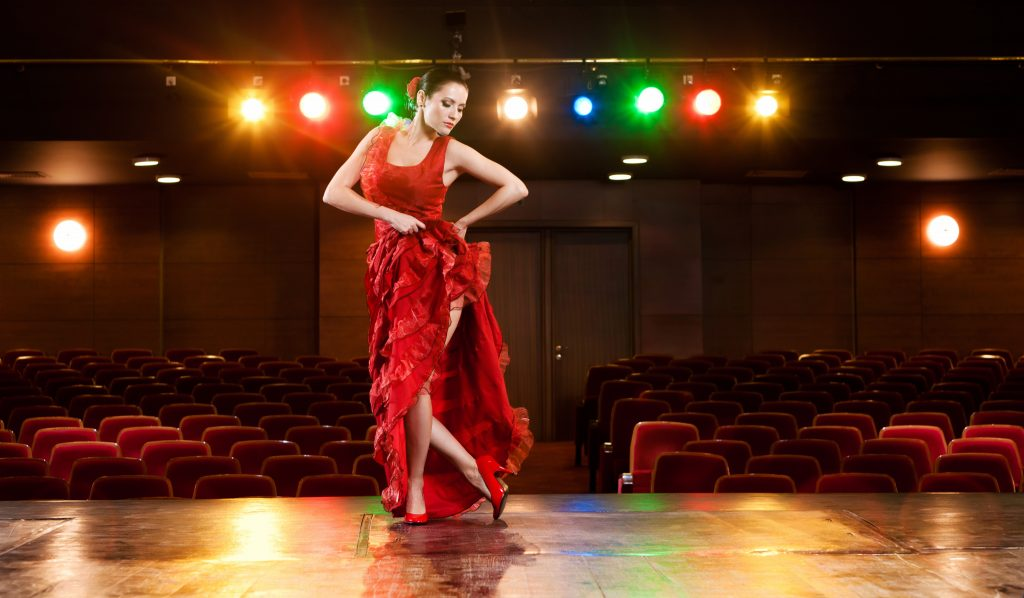 Sexy flamenco dancer performing her dance in a red long dress.
