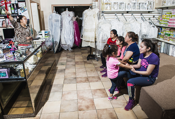 Friends and customers chat inside Mayra Orozco's quinceañera shop on Jefferson. Orozco is one of many Mexican immigrants who have found the American dream of business ownership on the boulevard. (Photo by Danny Fulgencio)
