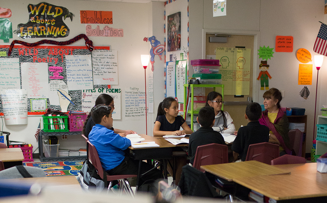 A group of 5th graders listen to their teacher Eva Trevino during a book review discussion at Felix G. Botello Elementary. (Photo by Rasy Ran)