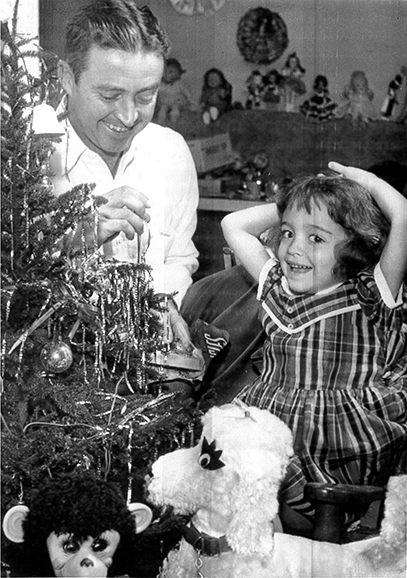 A.C. Bartlett decorates a Christmas tree with his daughter in this December 1954 news wire photo. (Photo courtesy of United press telephoto)