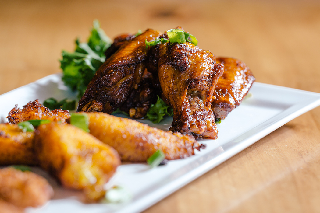 An appetizer of jerk chicken wings and fried plantains. (Photo by Kathy Tran)