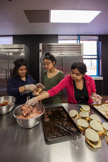 Karen Gallegos, Ileana Garcia and Diana Sanchez, students in Molina's culinary program, prepare lunch for M.J.'s cafe. See page 22 for details on the restaurant, which is open to the public. (Photo by Rasy Ran)