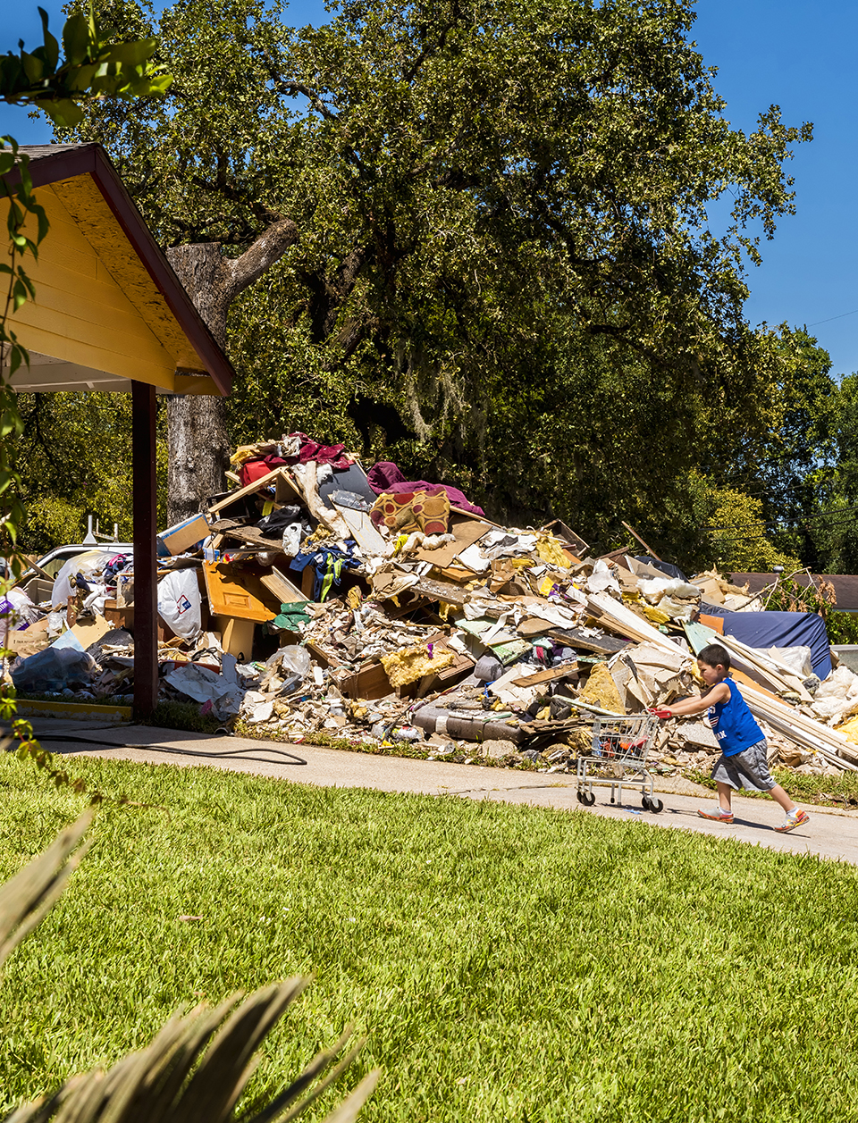 A boy plays in a driveway before a hill of refuse in northeast Houston. Previous page: A Texas flag wrapped around a palm tree at an RV park in Port Aransas. (Photo by Danny Fulgencio)