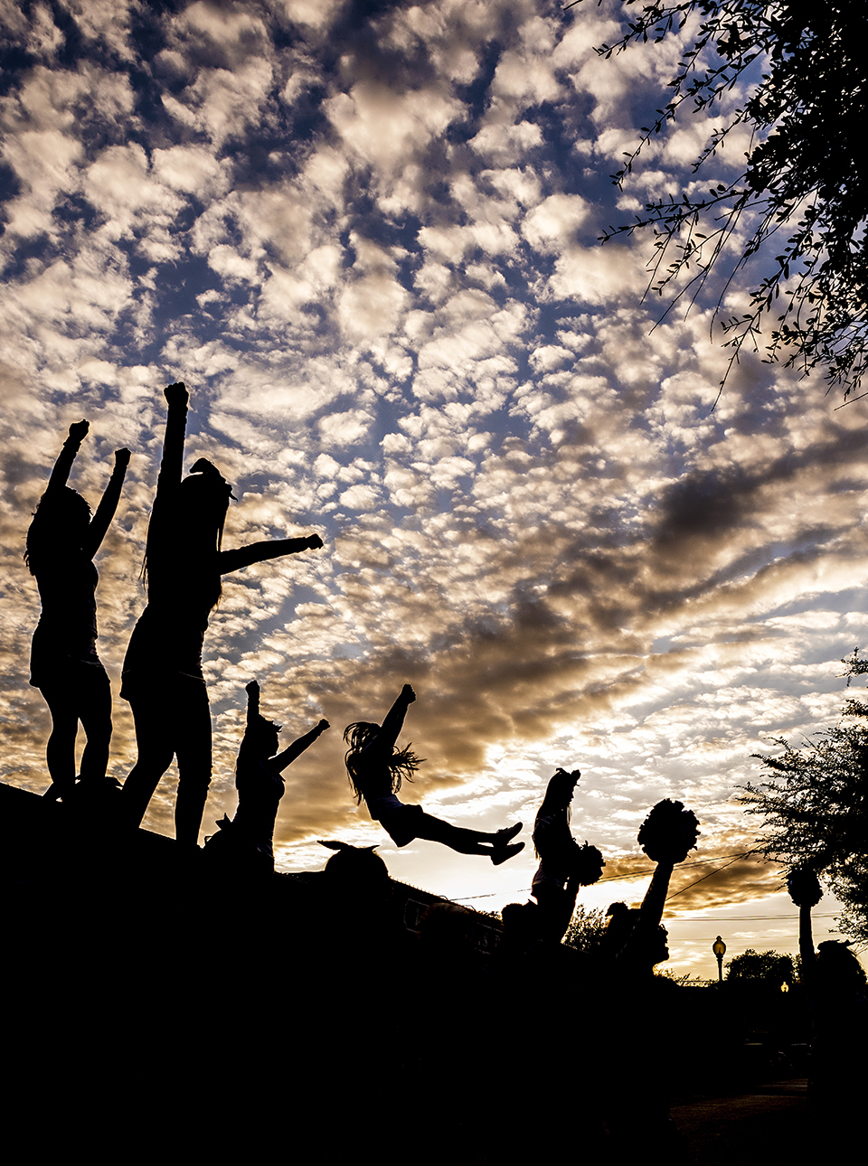 Cheerleaders are silhouetted in the afternoon sky during the annual Adamson vs. Sunset pep rally in the Bishop Arts District in September. Go Oak Cliff began throwing annual pep rallies for the intra-neighborhood football rivalry in 2012. (Photo by Danny Fulgencio)